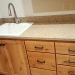 Quartz laundry counter with overmount sink and quartz backsplash